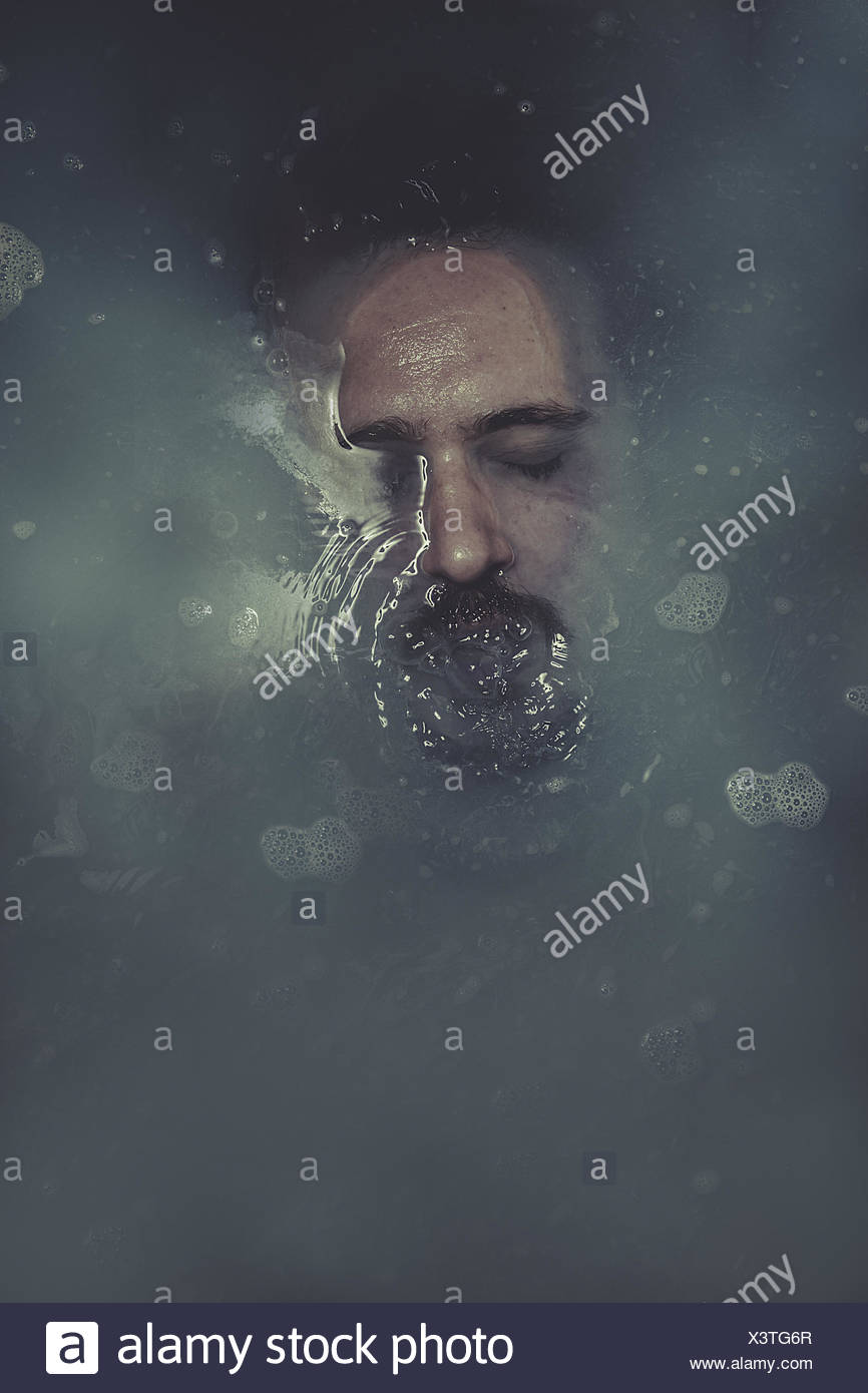 concept suicide, man submerged in blue water Stock Photo