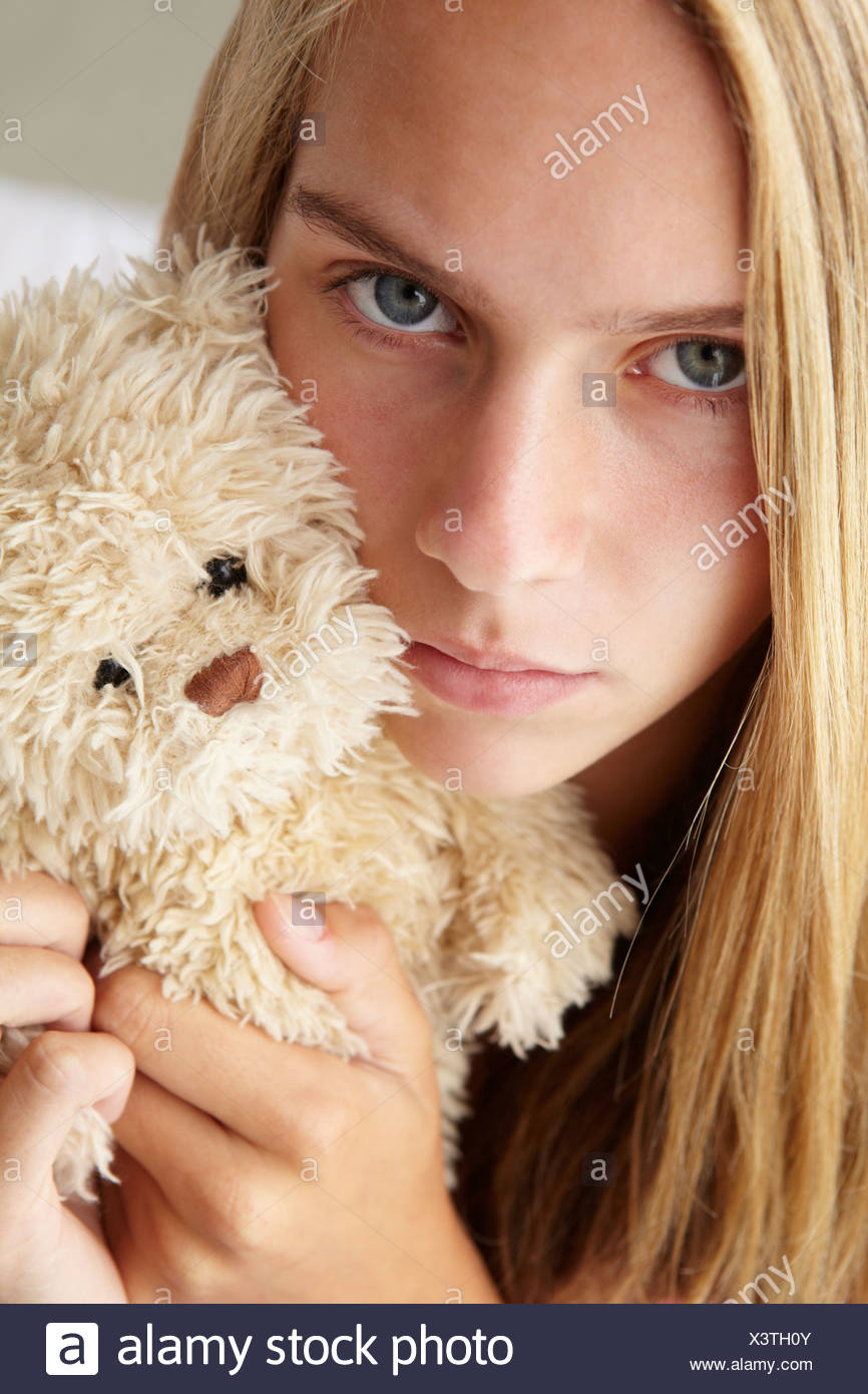 Unhappy teenage girl with cuddly toy - Stock Image