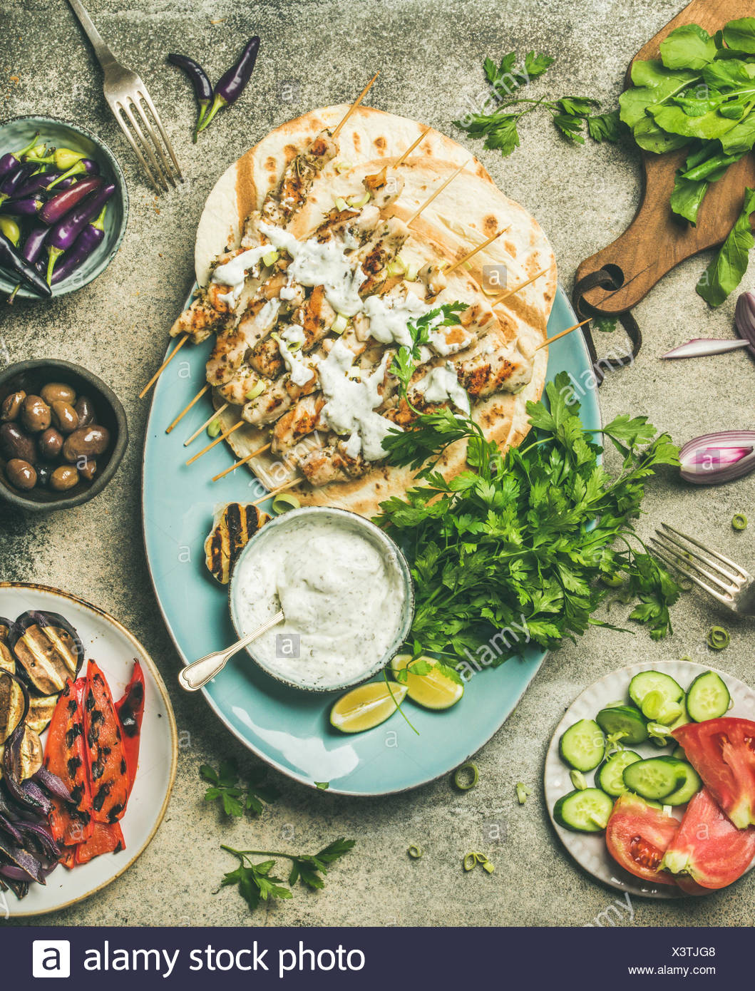 Summer barbecue party dinner set. Flatlay of grilled chicken skewers with yogurt dip, flatbreads, fresh parsley, vegetables, marinated olives and chil - Stock Image