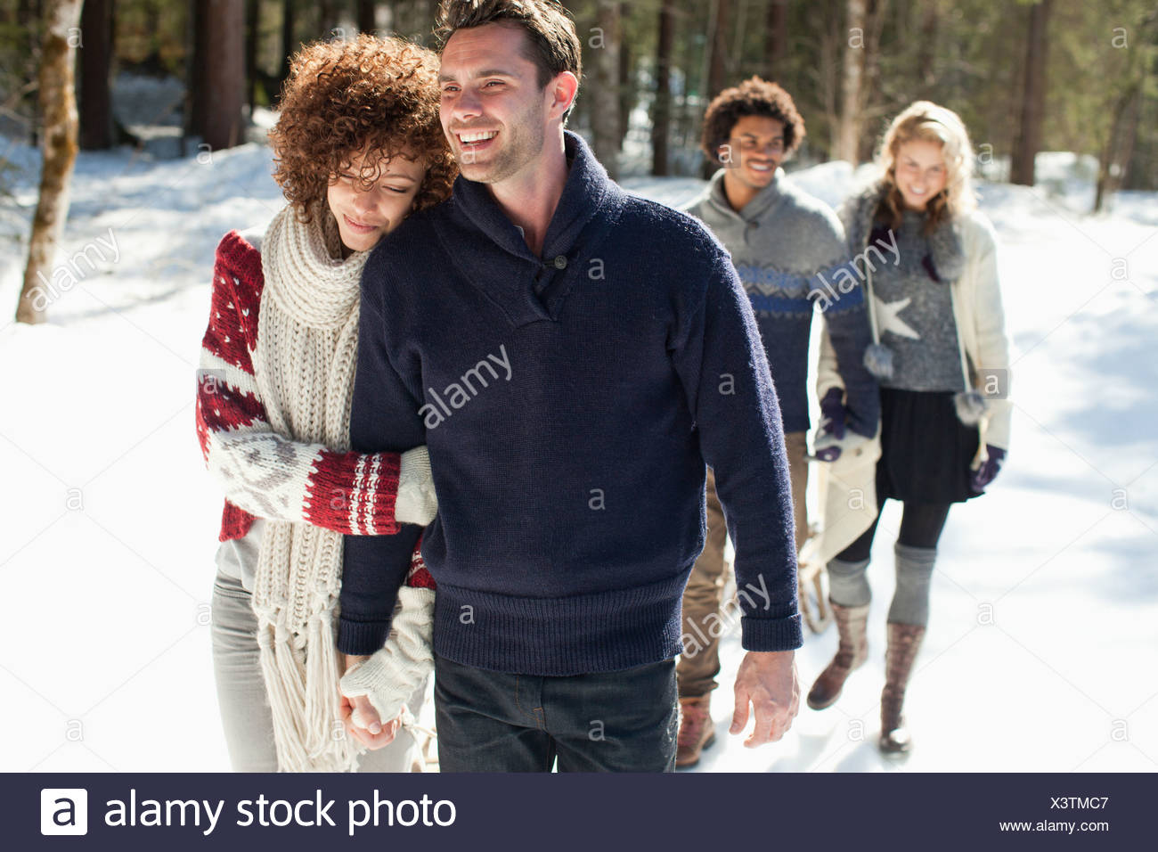 Two couples walking in snow - Stock Image