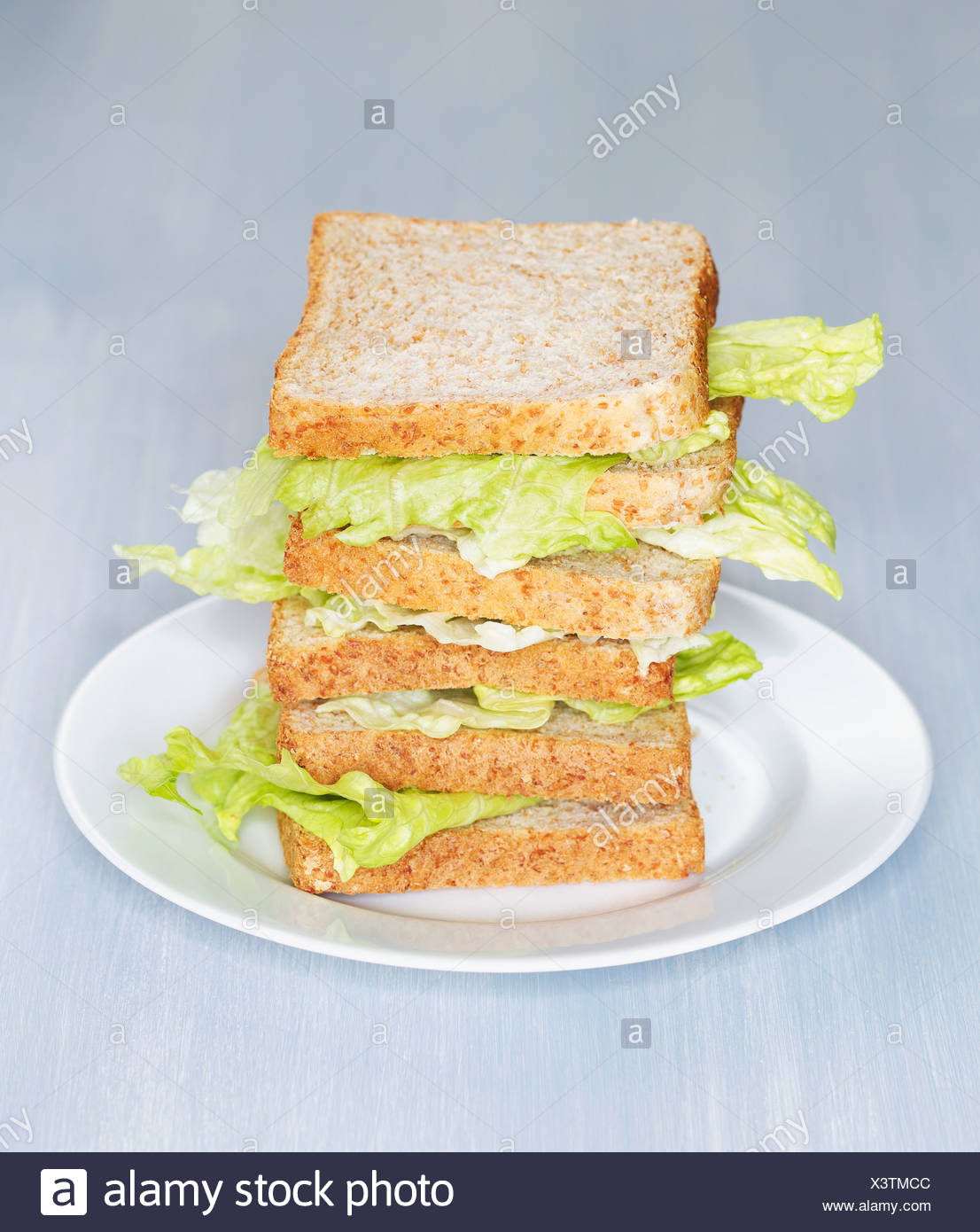 Stacked wholemeal toast slices with Iceberg Salad on plate - Stock Image