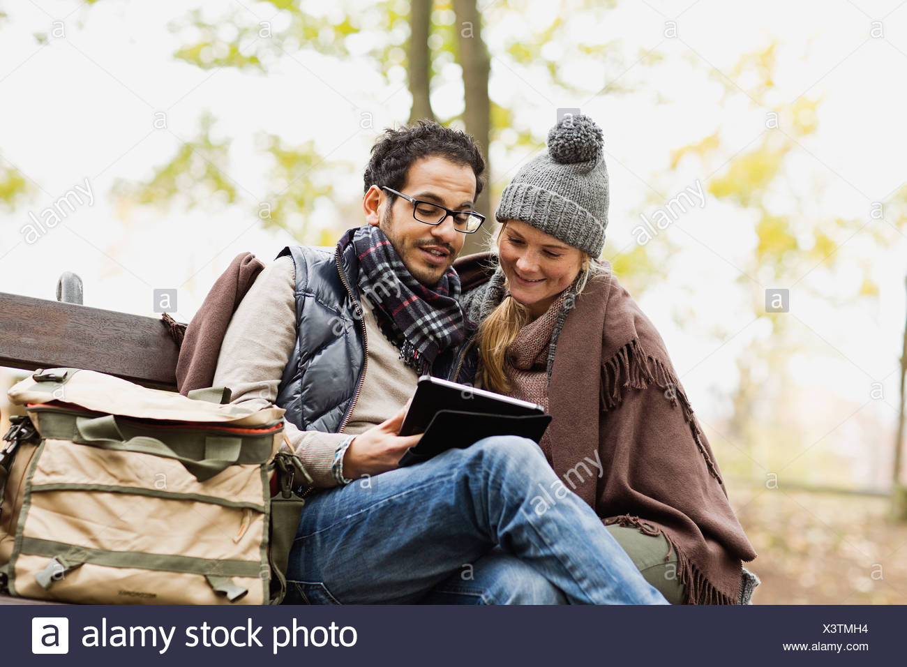 Couple using tablet computer in park Stock Photo
