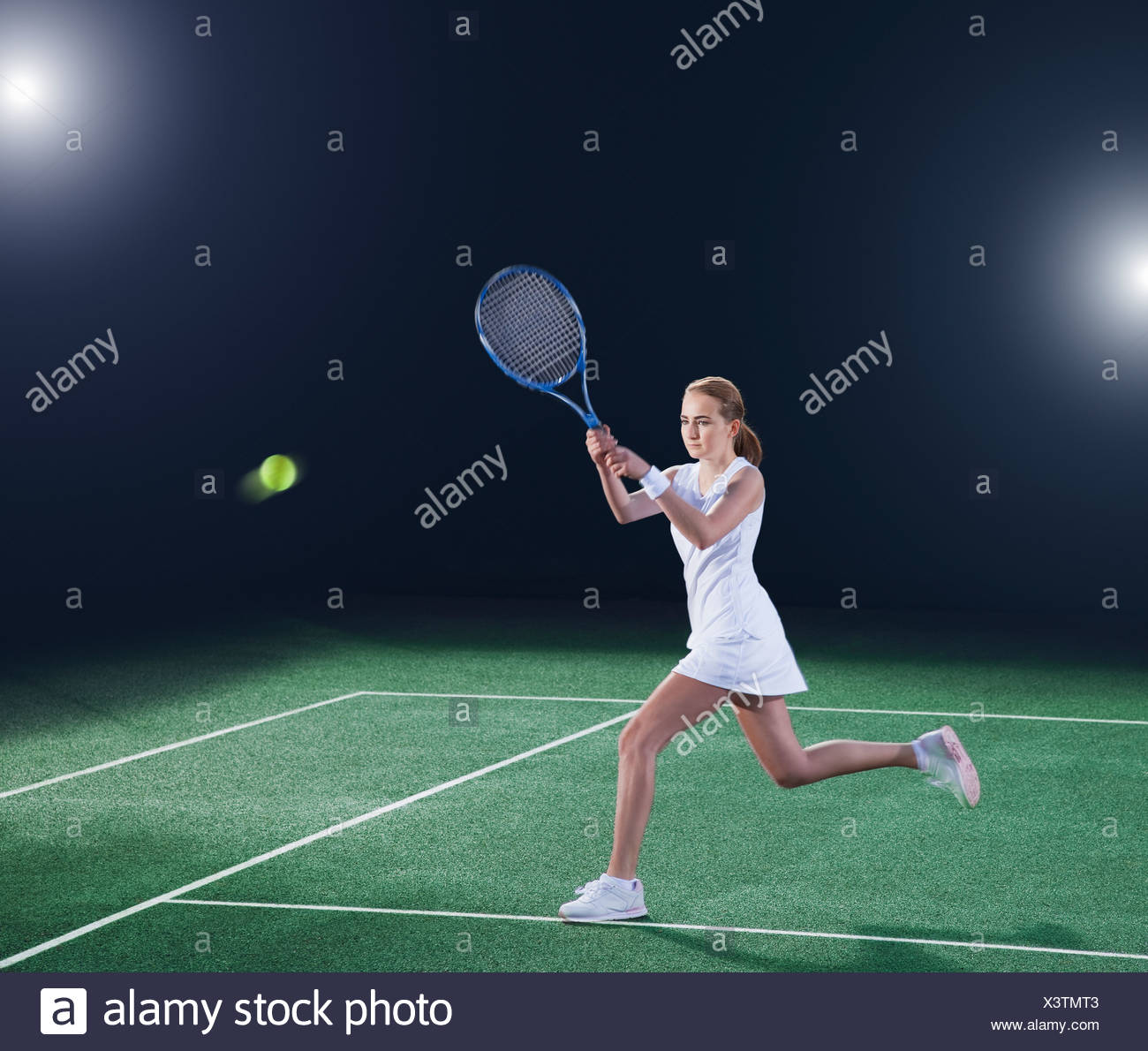 Tennis player hitting ball on court - Stock Image