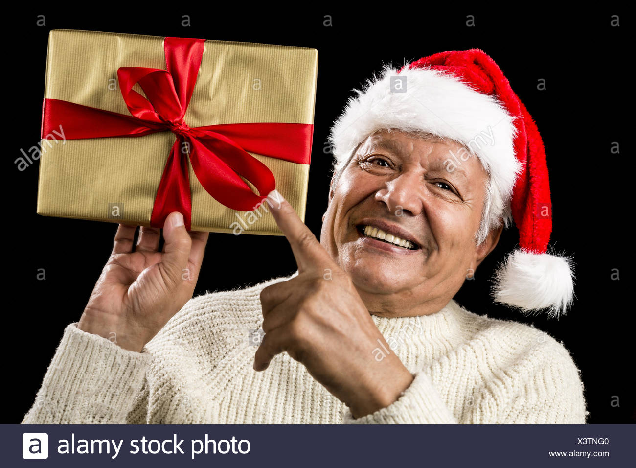 Avid Aged Man Pointing At Golden Wrapped Present Stock Photo