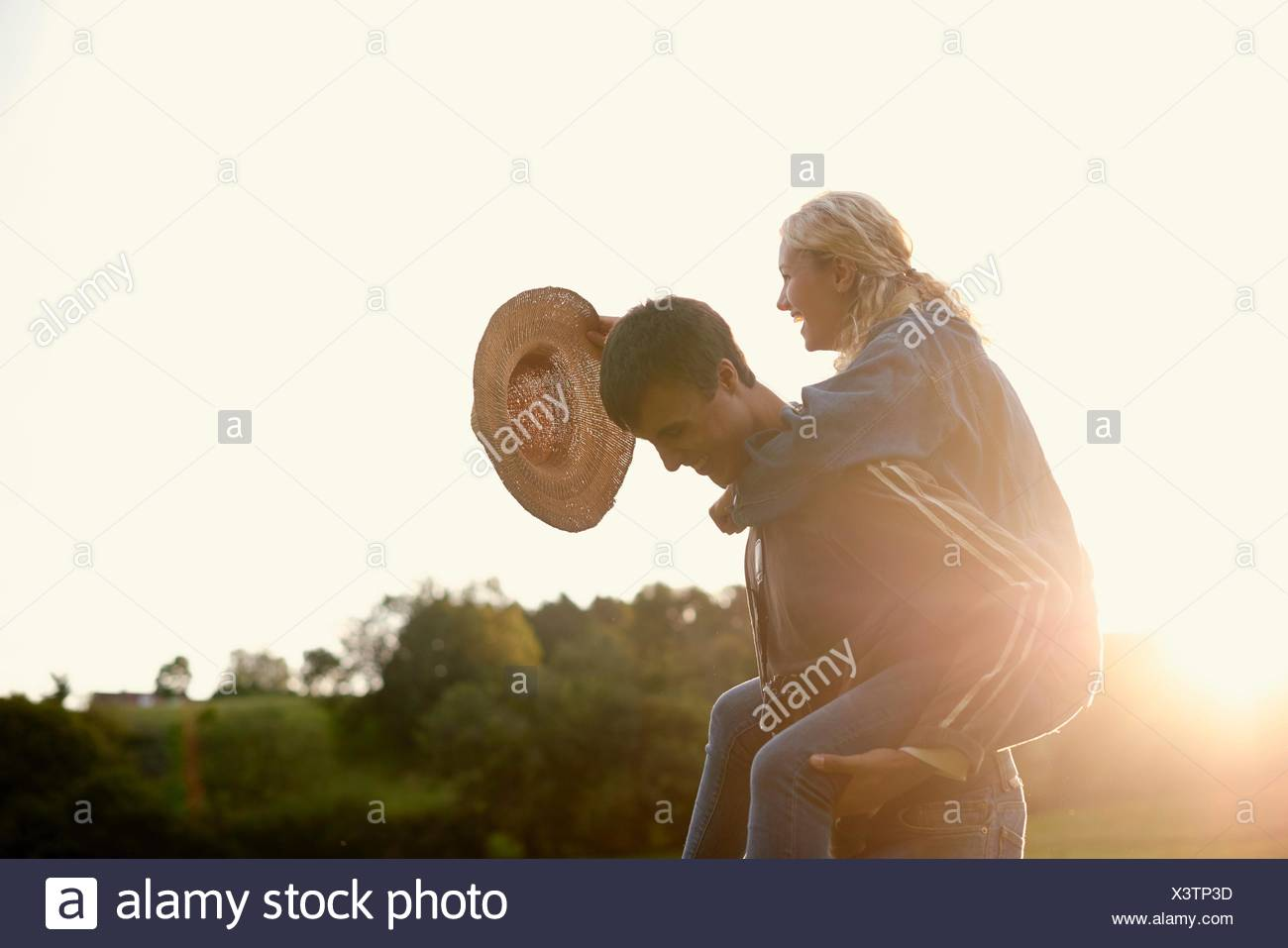 Young man giving girlfriend a piggyback - Stock Image