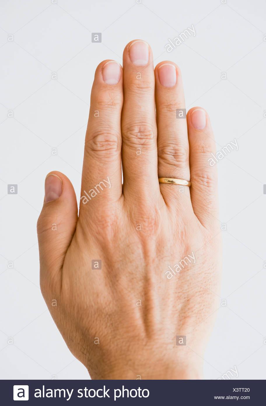 Close up of man's hand wearing wedding ring - Stock Image