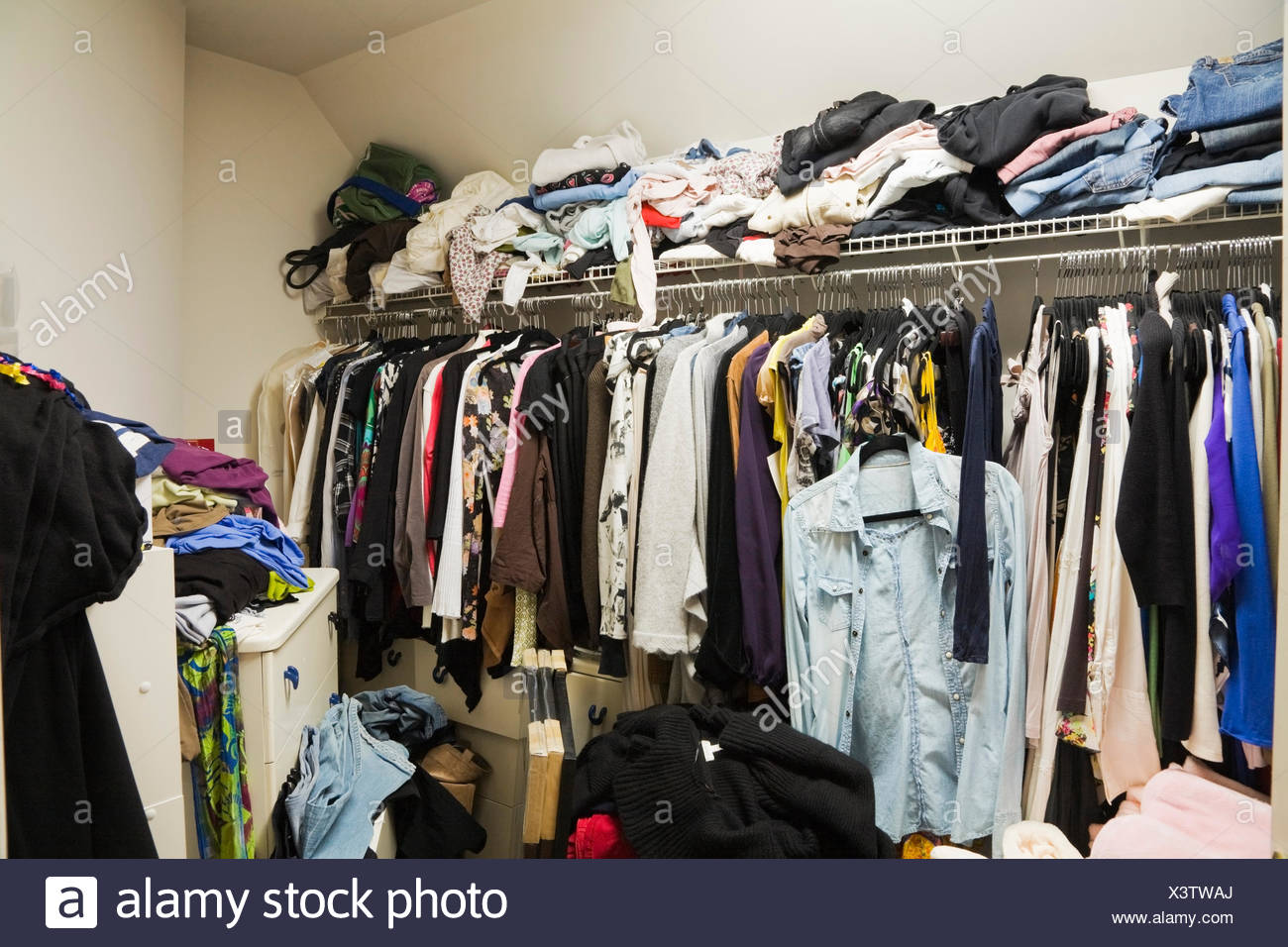 Walk-in closet filled with woman's clothes inside a luxurious cottage style residential home, Montreal, Quebec, Canada - Stock Image
