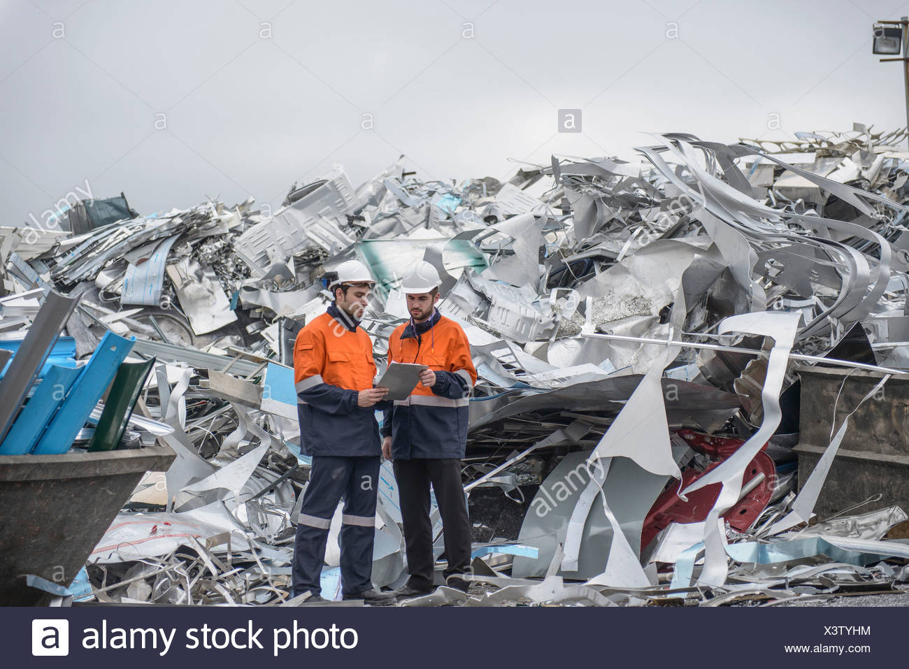 Two workers looking at clip board in front of scrap aluminum - Stock Image