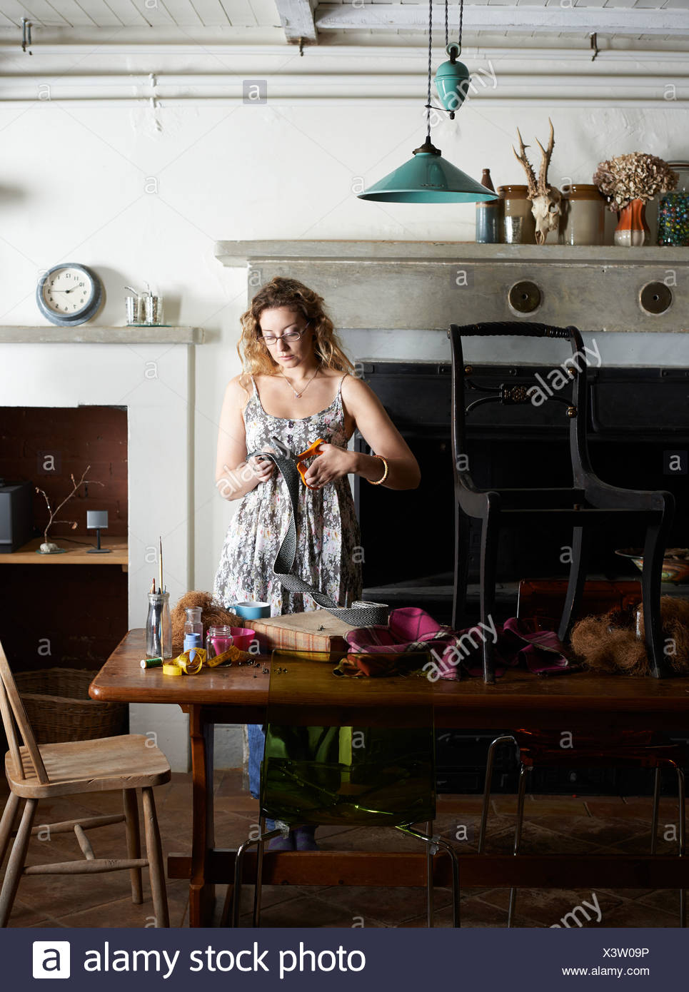 Woman decorating chair with fabric - Stock Image