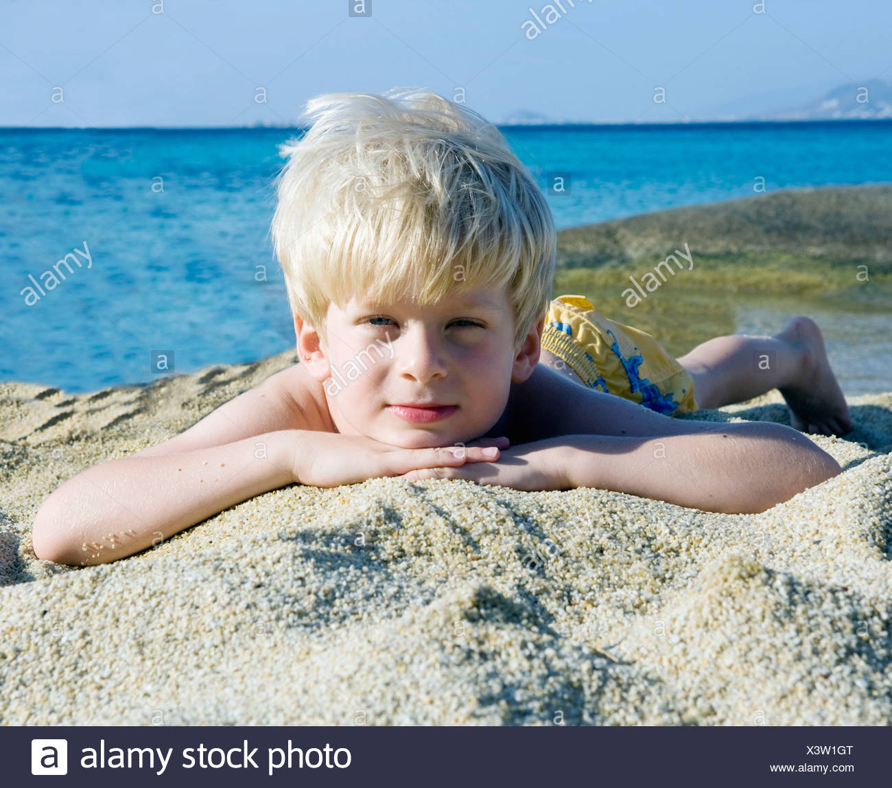 Young boy lying in the sand at the beach. Stock Photo