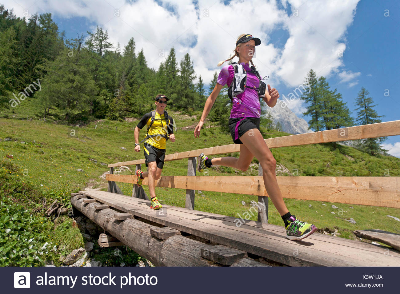 young couple running over a wooden bridge over a brook while trail running in the Dachstein Mountains, Austria, Styria, Dachstein - Stock Image