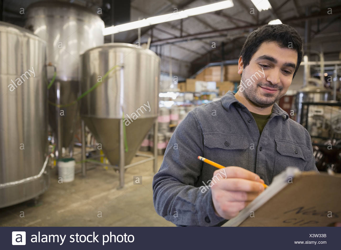 Brewery worker with clipboard near vats - Stock Image