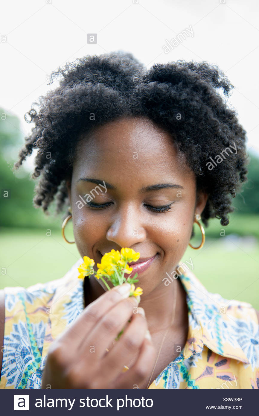 Portrait of a woman holding a yellow flower. - Stock Image