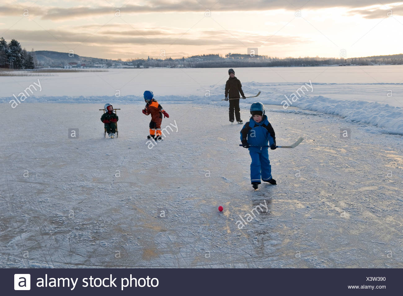 Children playing ice hockey on frozen lake - Stock Image