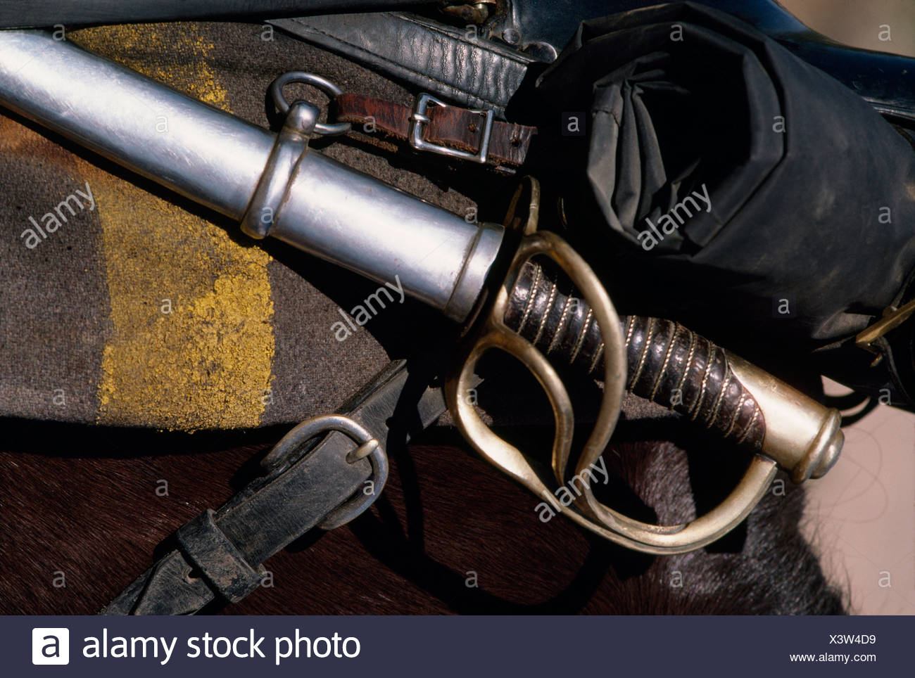 Close up of a sword hilt and scabbard mounted on a horse saddle. - Stock Image
