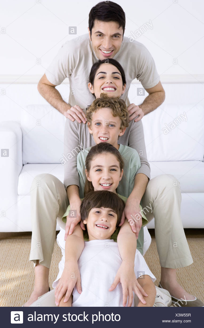 Portrait of family lined up one behind the other, shortest to tallest - Stock Image