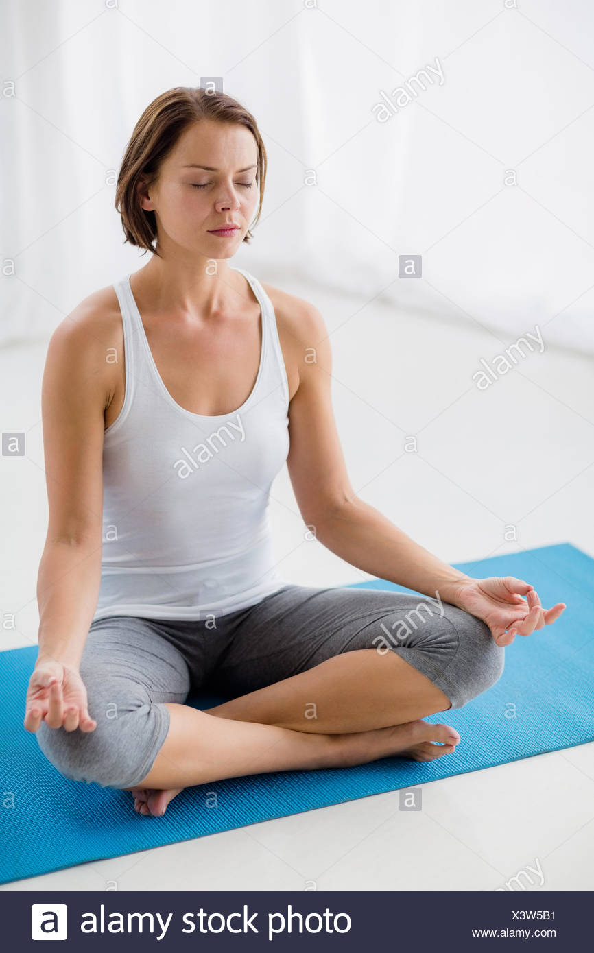 Full length of woman performing yoga - Stock Image