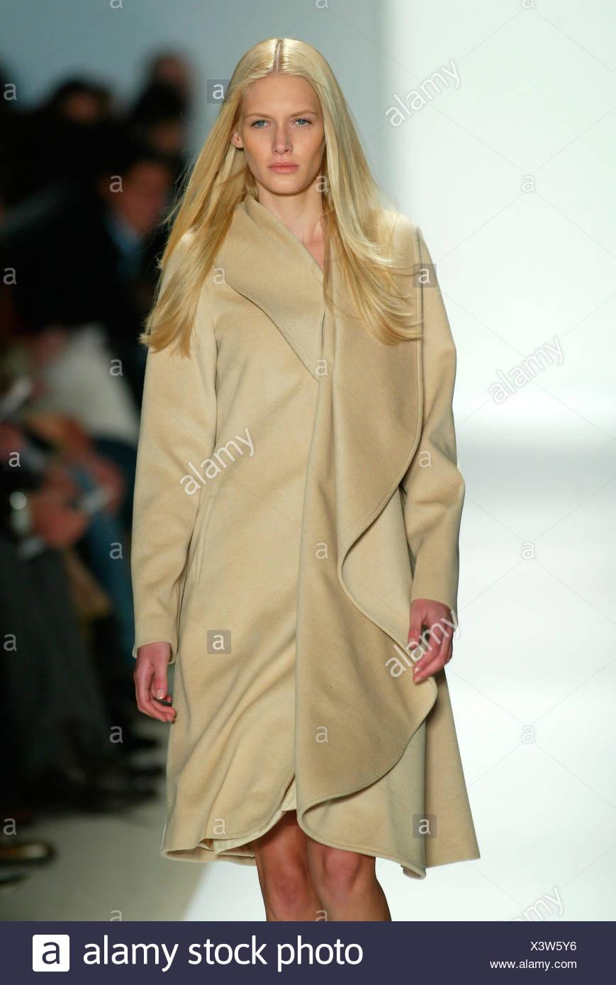 Luca Luca New York Ready to Wear Autumn Winter Blonde female model wearing a knee length camel drape coat - Stock Image