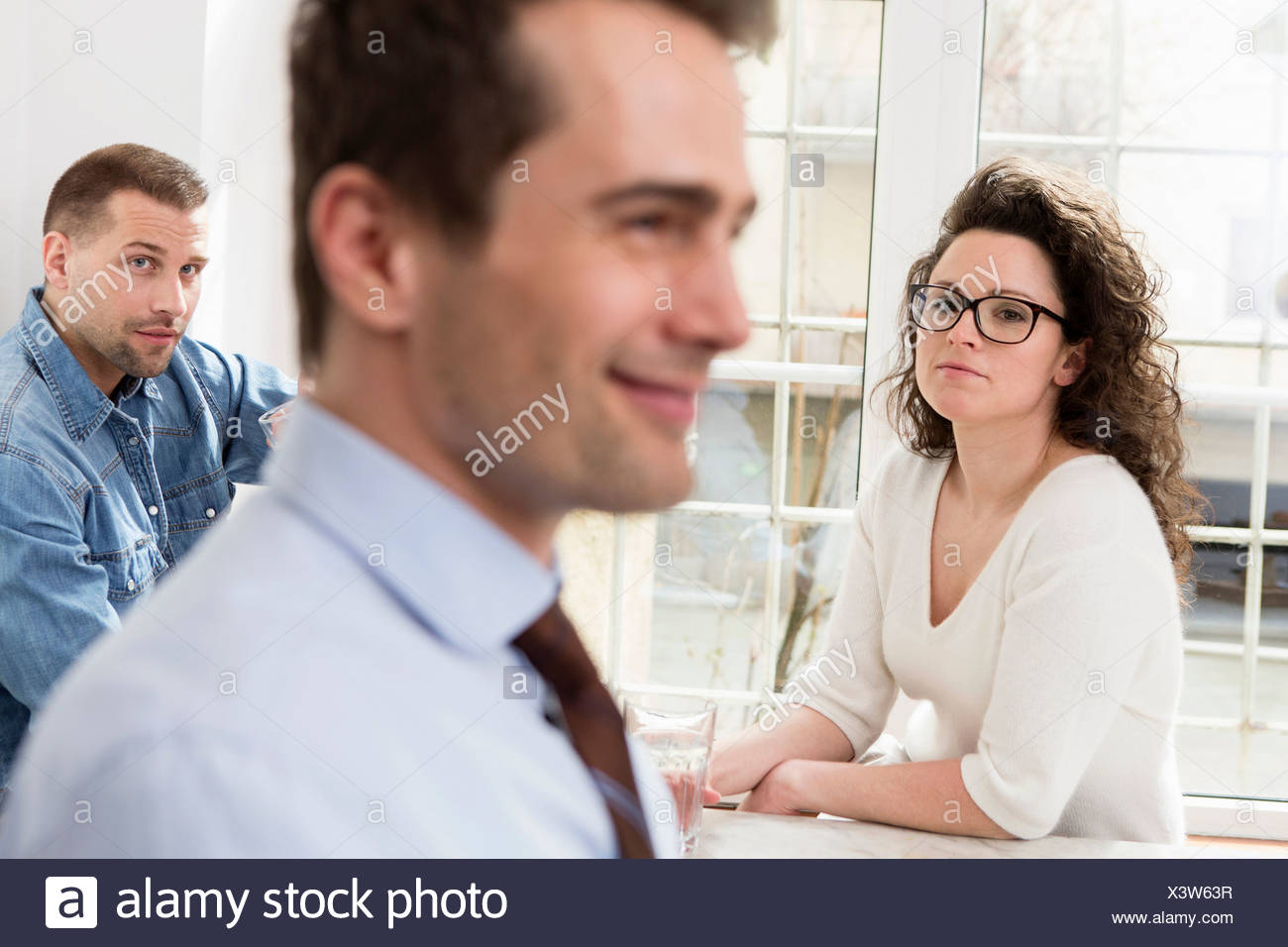Mature man smiling, mid adults in background - Stock Image