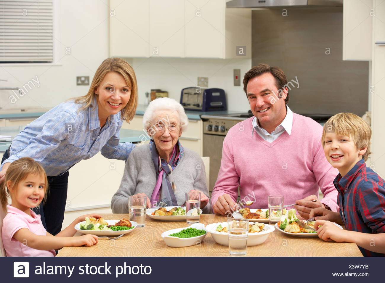 Multi-generation family sharing meal together - Stock Image