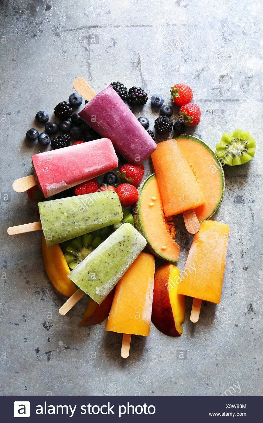 Popsicles with kiwi,mango,cantaloupe,blueberry,blackberry and strawberry over fresh fruit.Top view - Stock Image