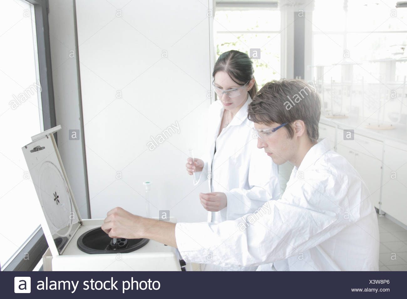 Chemistry students using equipment in laboratory - Stock Image