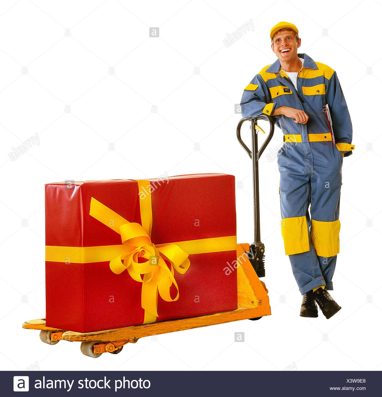 Messenger, happy, elevating platform trucks, present, professions, man, friendly, friendliness, overall, working clothes, occupation, parcel deliver, package delivery, package, surprise, gigantic package, envelope, red, loop, mesh, yellow, studio, cut out, - Stock Image