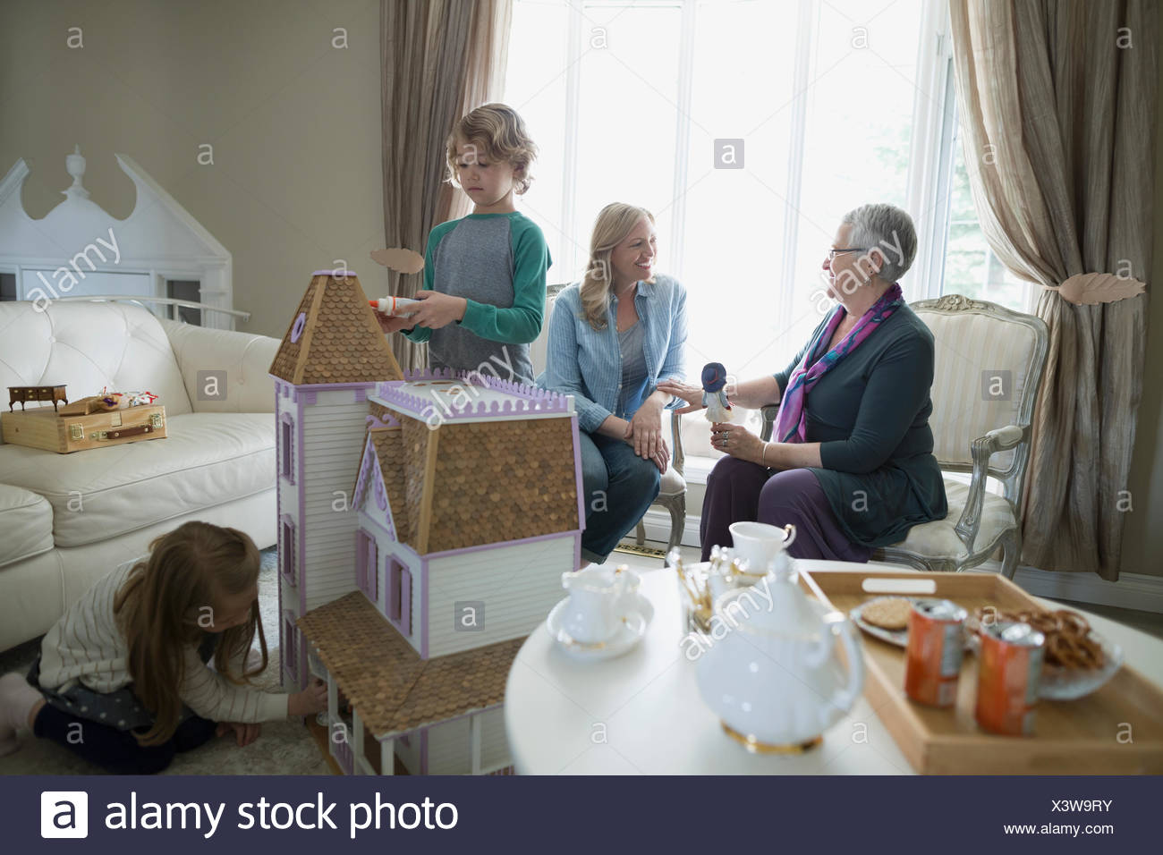 Children playing with dollhouse while mother and grandmother talk - Stock Image