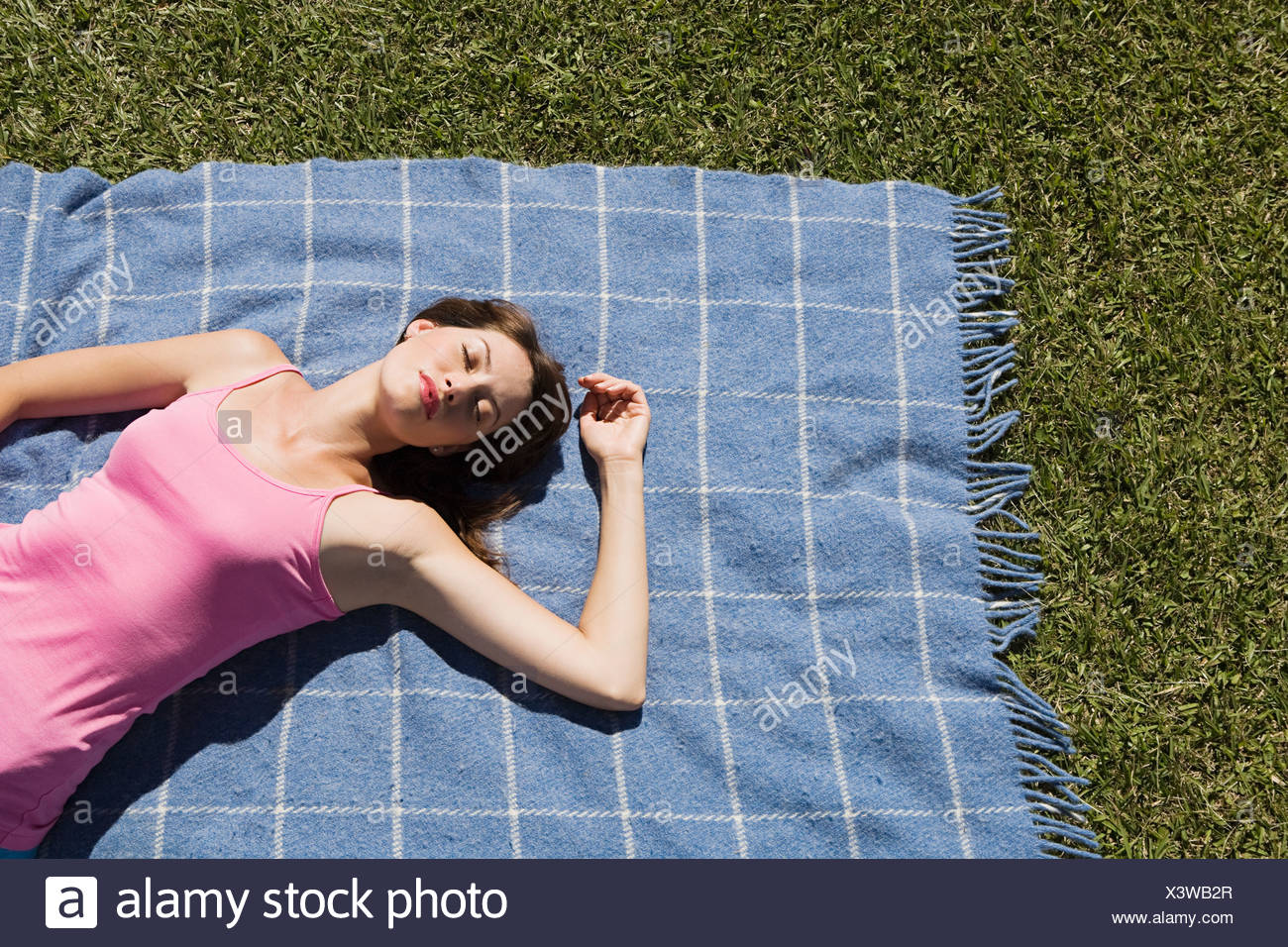 Woman lying on picnic blanket with eyes closed - Stock Image