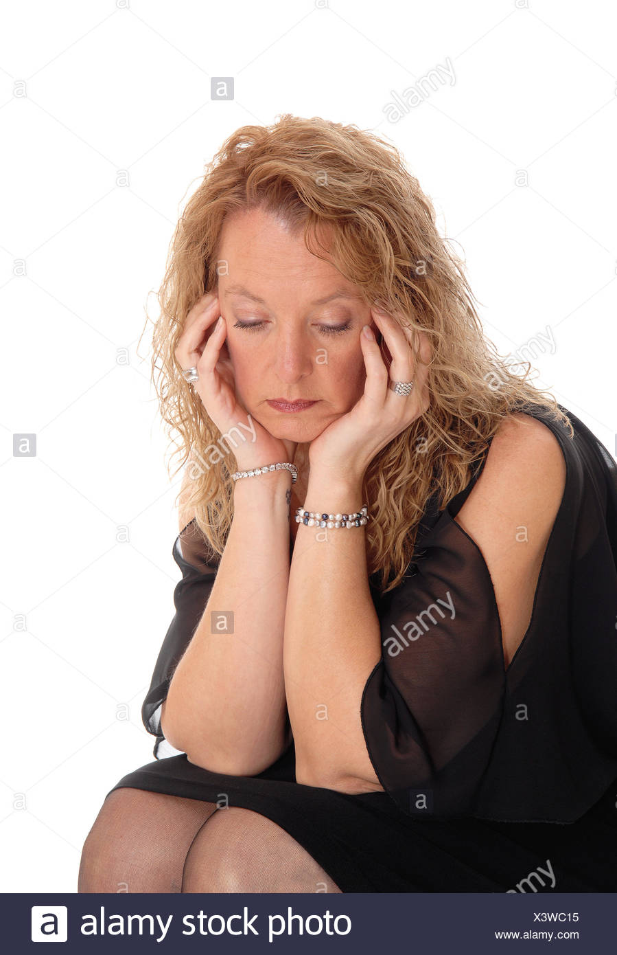A sad looking blond woman sitting. - Stock Image