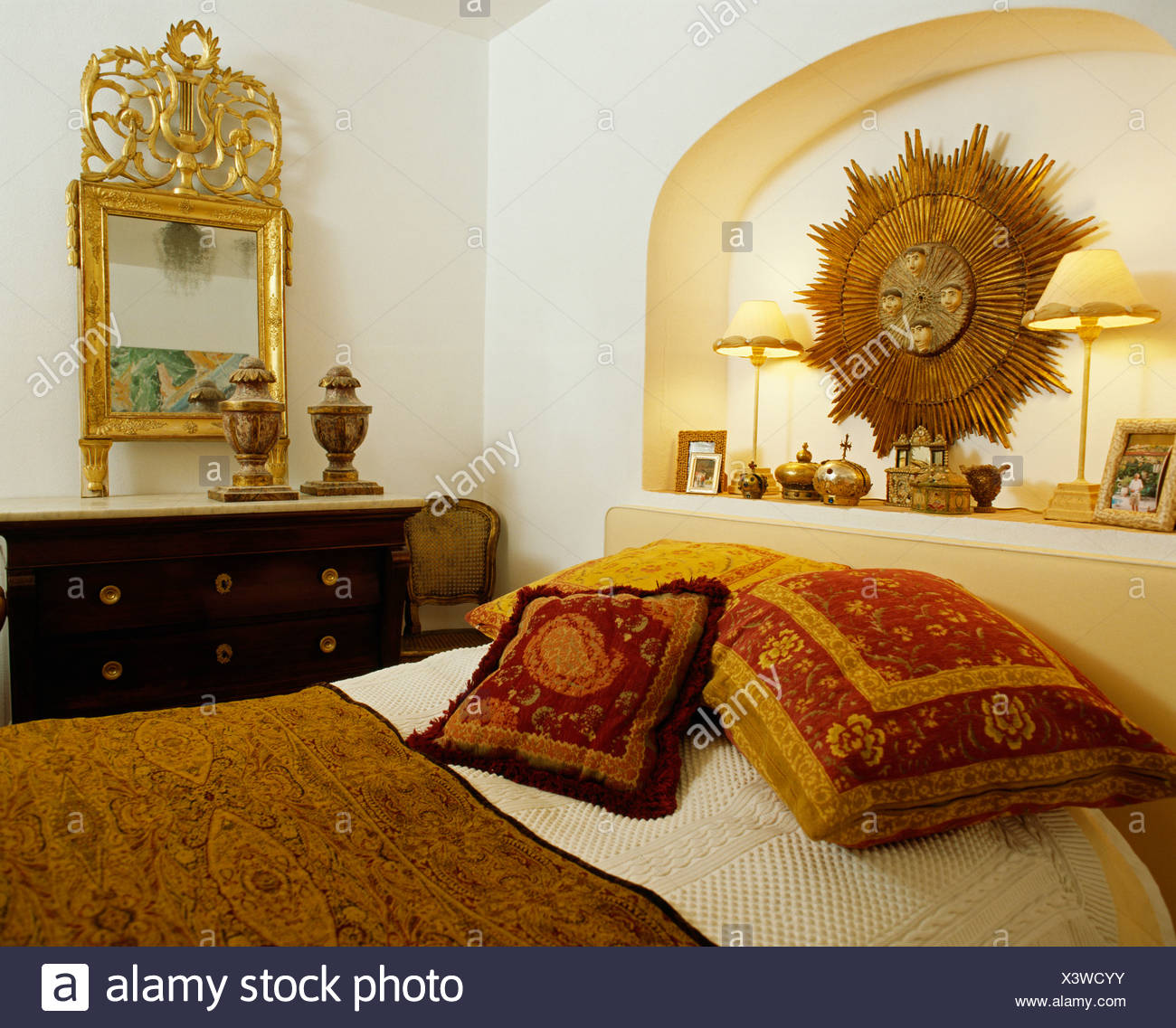 Antique Gold Sunburst In Alcove Above Bed With Tapestry Cushions In