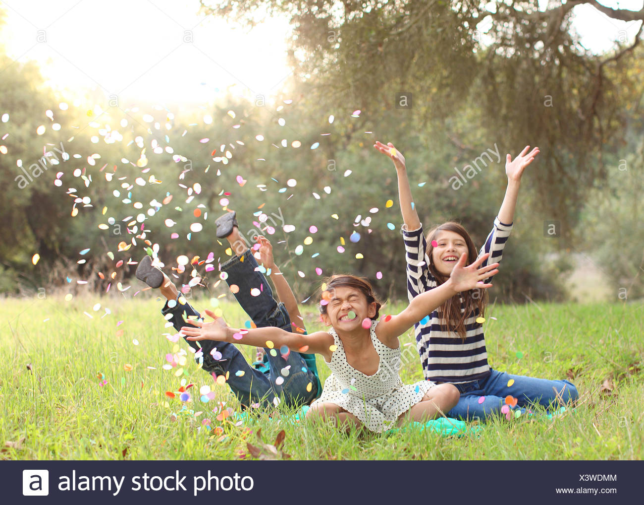 Three children sitting in park throwing confetti in air - Stock Image