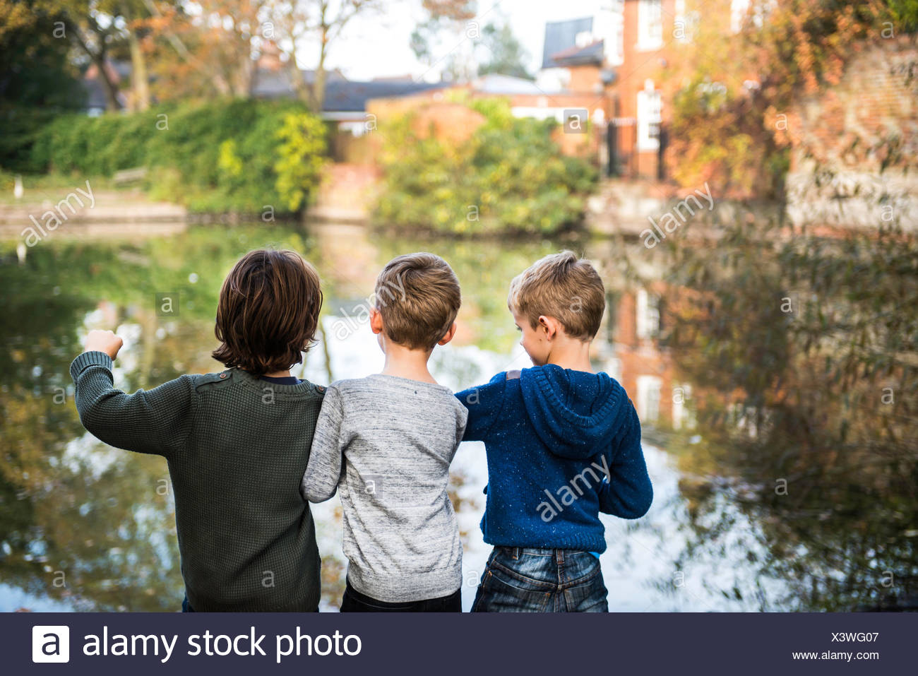 Three young boys, standing beside lake, rear view - Stock Image
