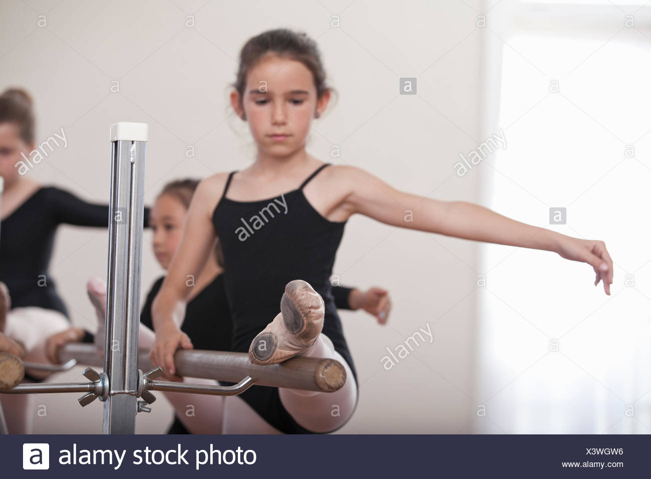 Young ballerina practicing at barre in ballet school - Stock Image