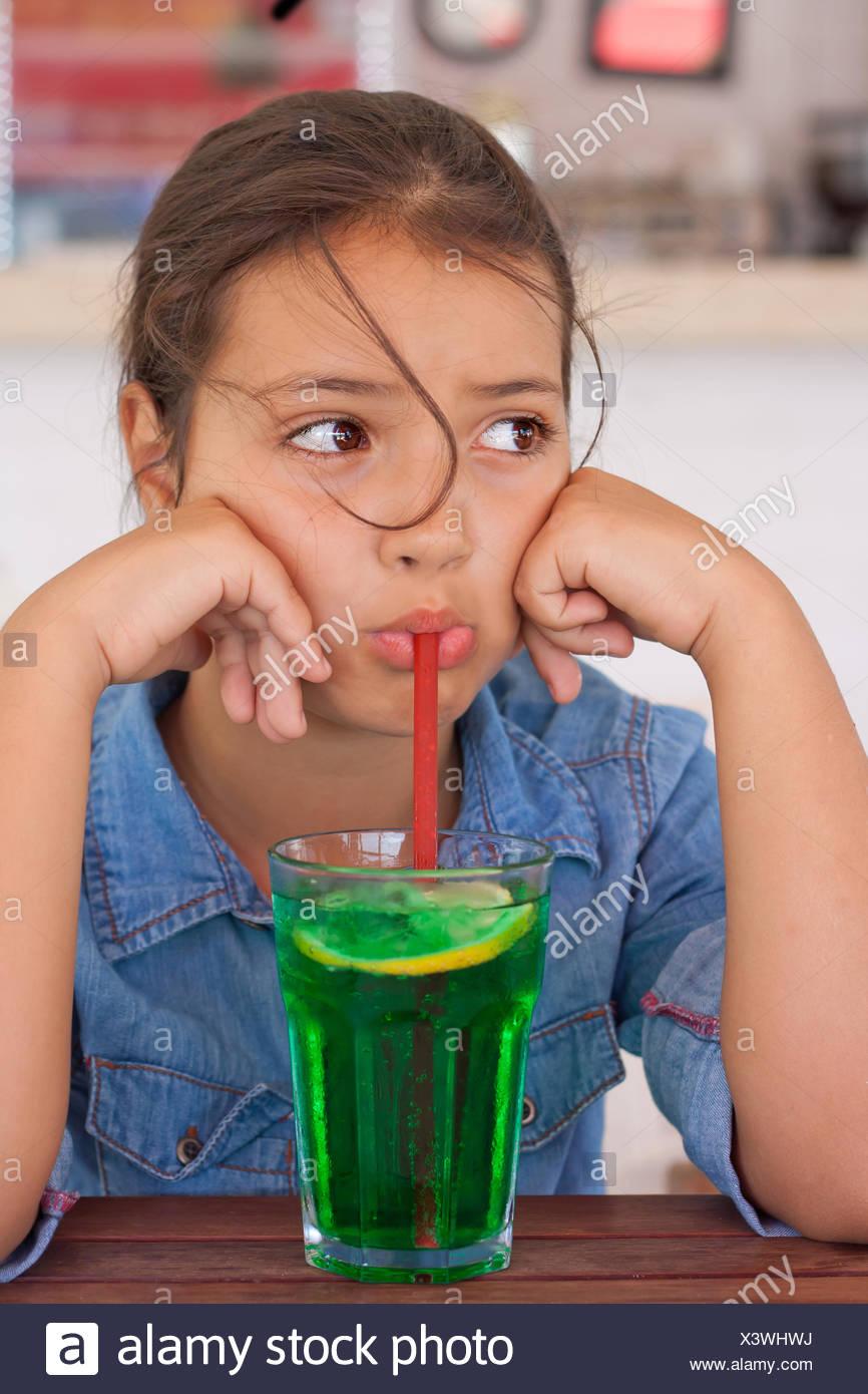 Grumpy girl drinking mocktail through a straw - Stock Image