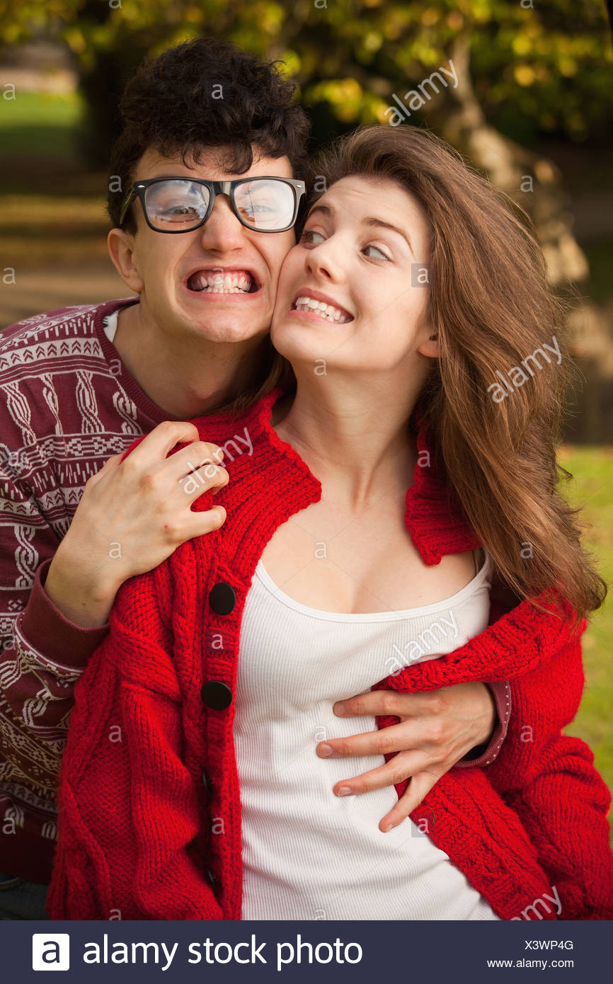 Teenage couple making faces in park - Stock Image