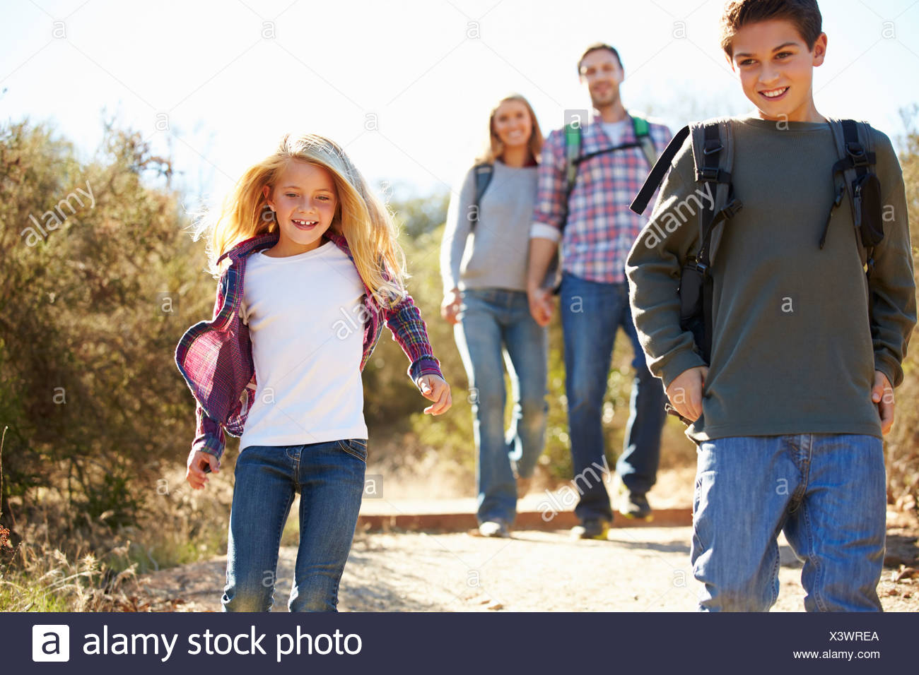 Mother And Children Hiking In Countryside Wearing Backpacks - Stock Image