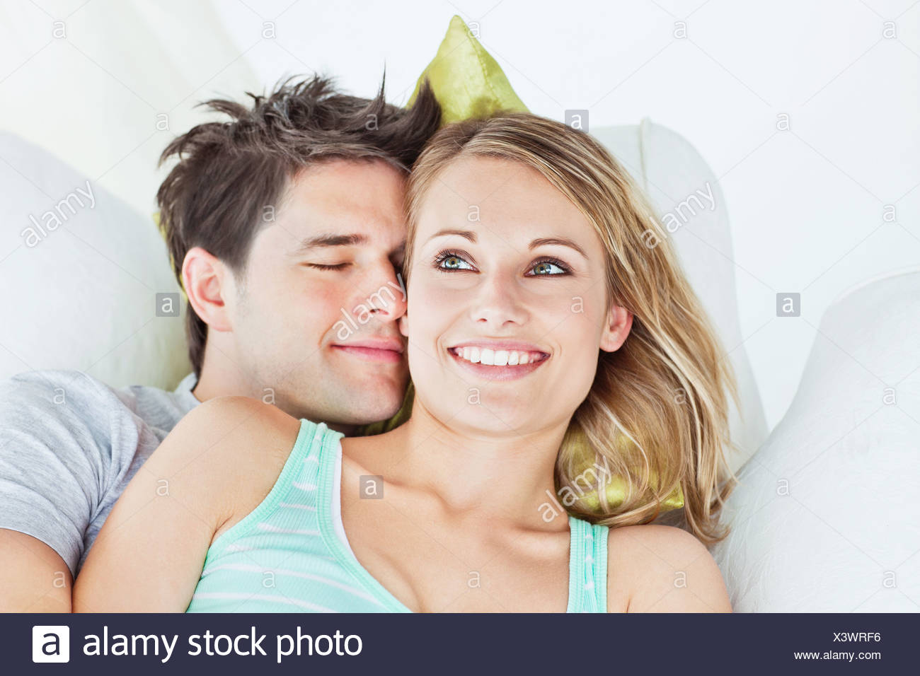 Loving yog couple lying on a sofa - Stock Image