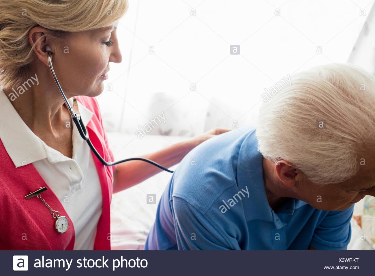 Nurse using stethoscope to take care of a senior man - Stock Image