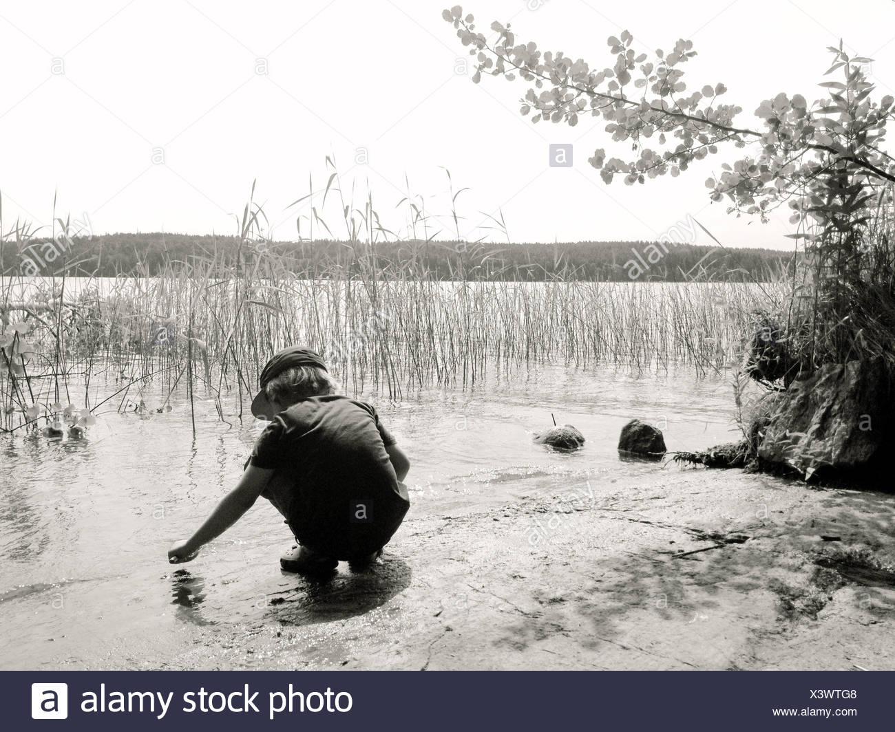 Boy playing by the edge of a  lake - Stock Image