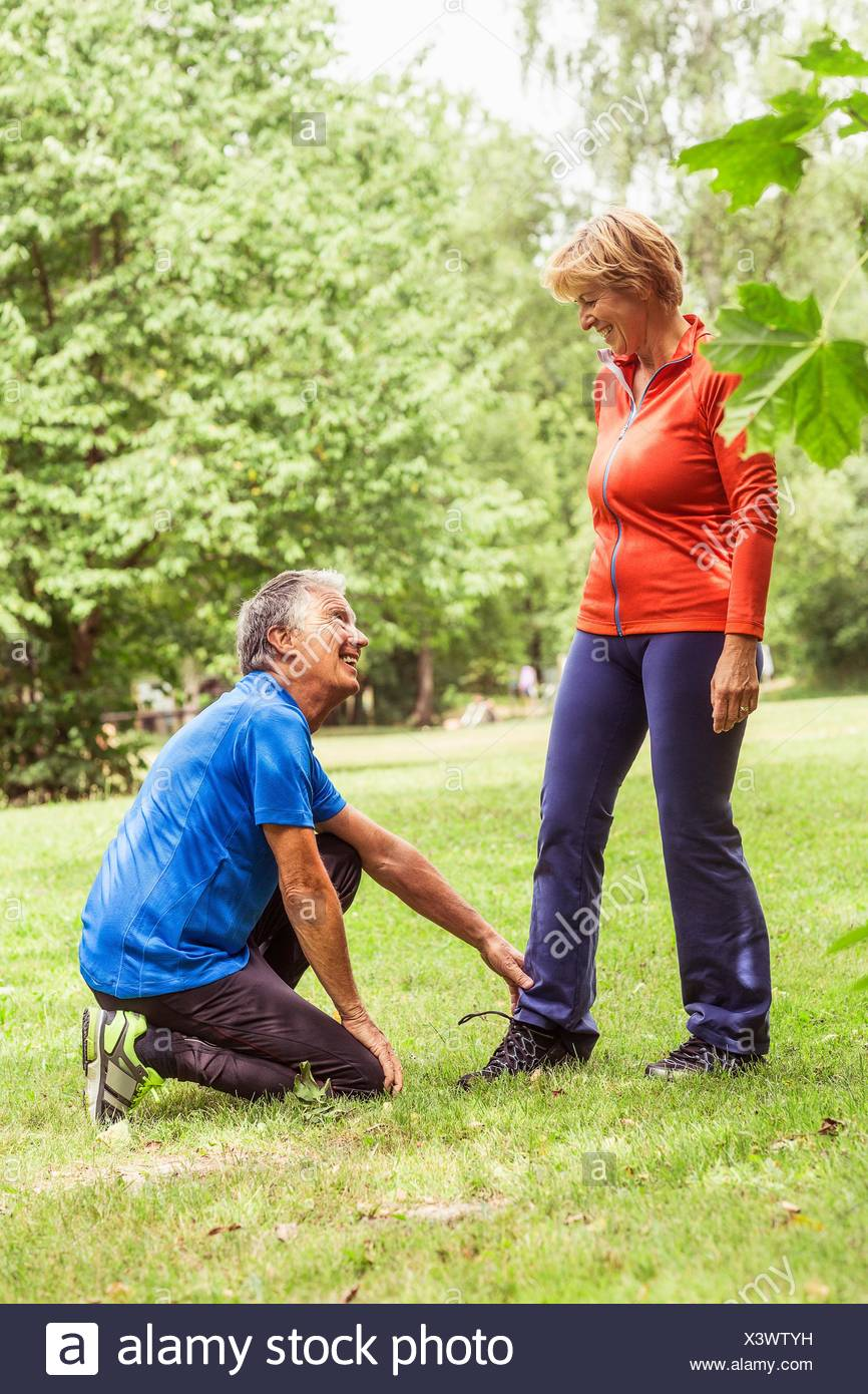 Couple exercising outdoors, senior man holding mature woman's ankle - Stock Image