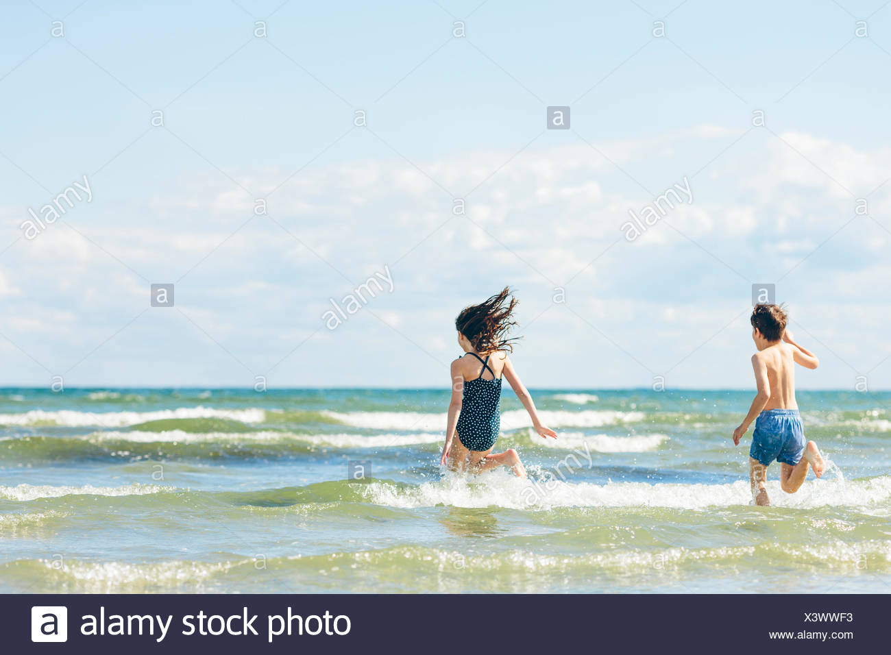 Girl (10-11) and boy (8-9) running into sea - Stock Image