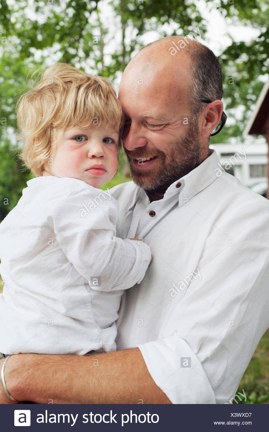 Sweden, Smaland, Kalvsvik, Man carrying grandson (2-3) - Stock Image
