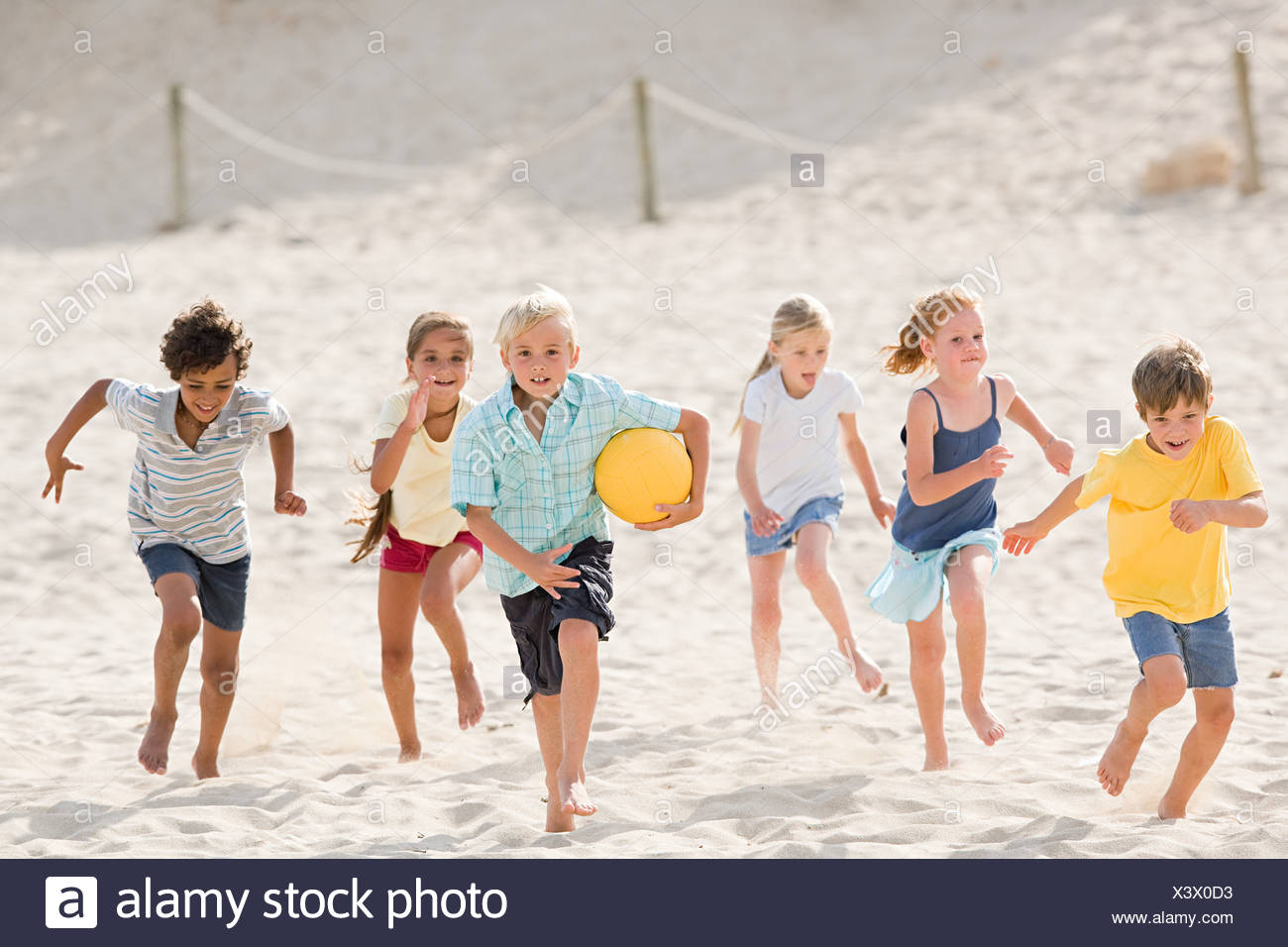 Children running across beach Stock Photo