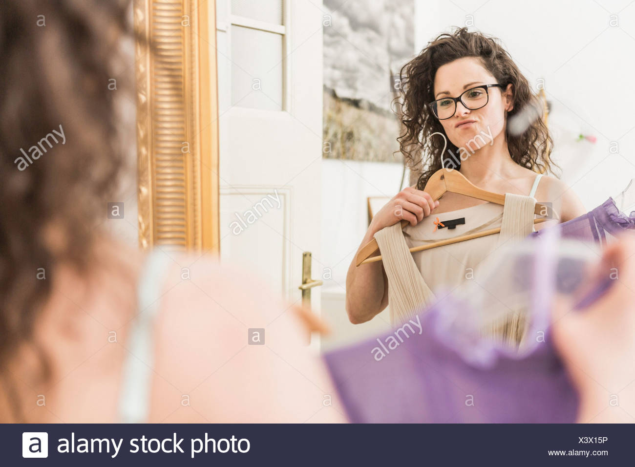 Mid adult woman holding up dress in front of mirror - Stock Image