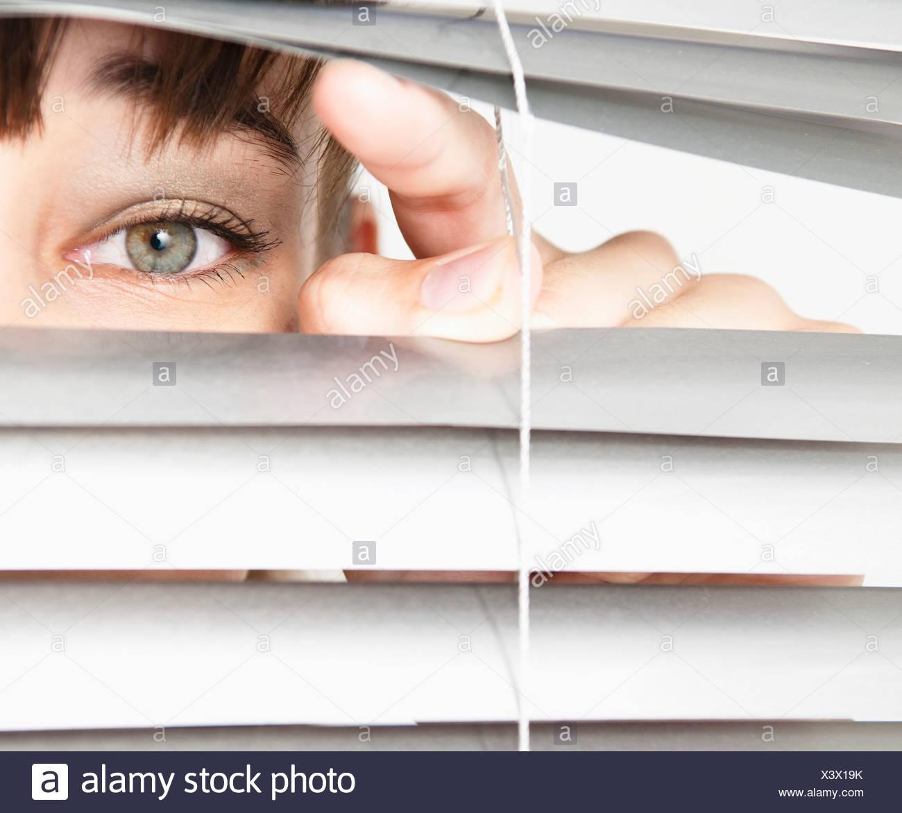 Woman peeking through blinds - Stock Image
