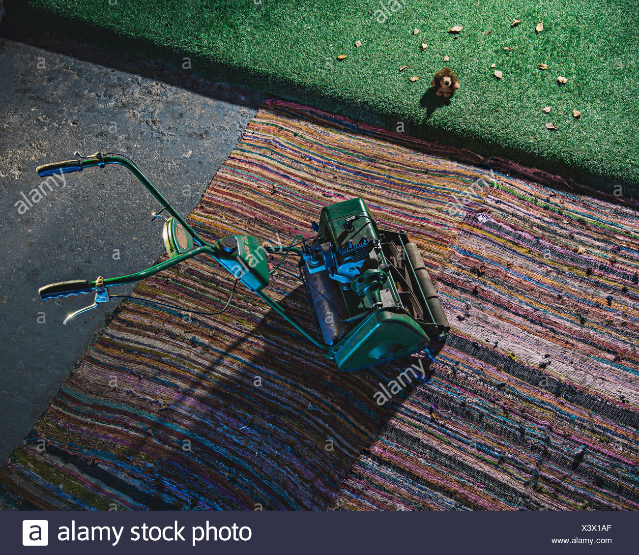 Lawnmower on rug with toy hedgehog - Stock Image