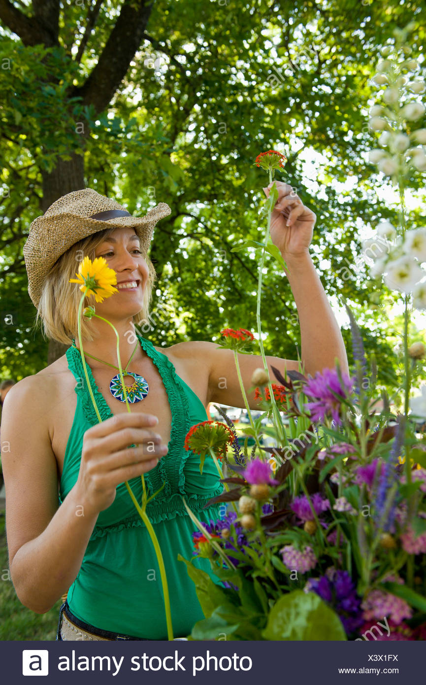 A young woman picks out flowers at a Farmer's Market. - Stock Image