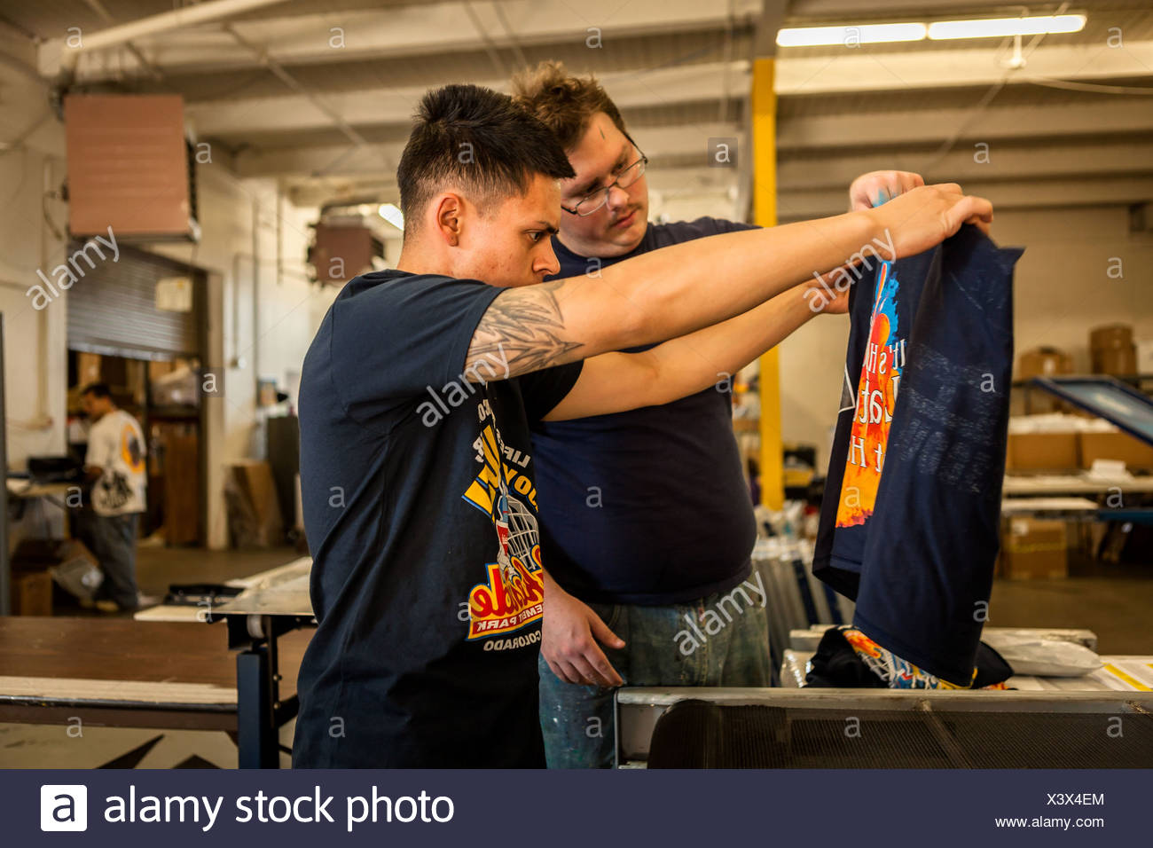 Workers checking quality in screen print workshop - Stock Image