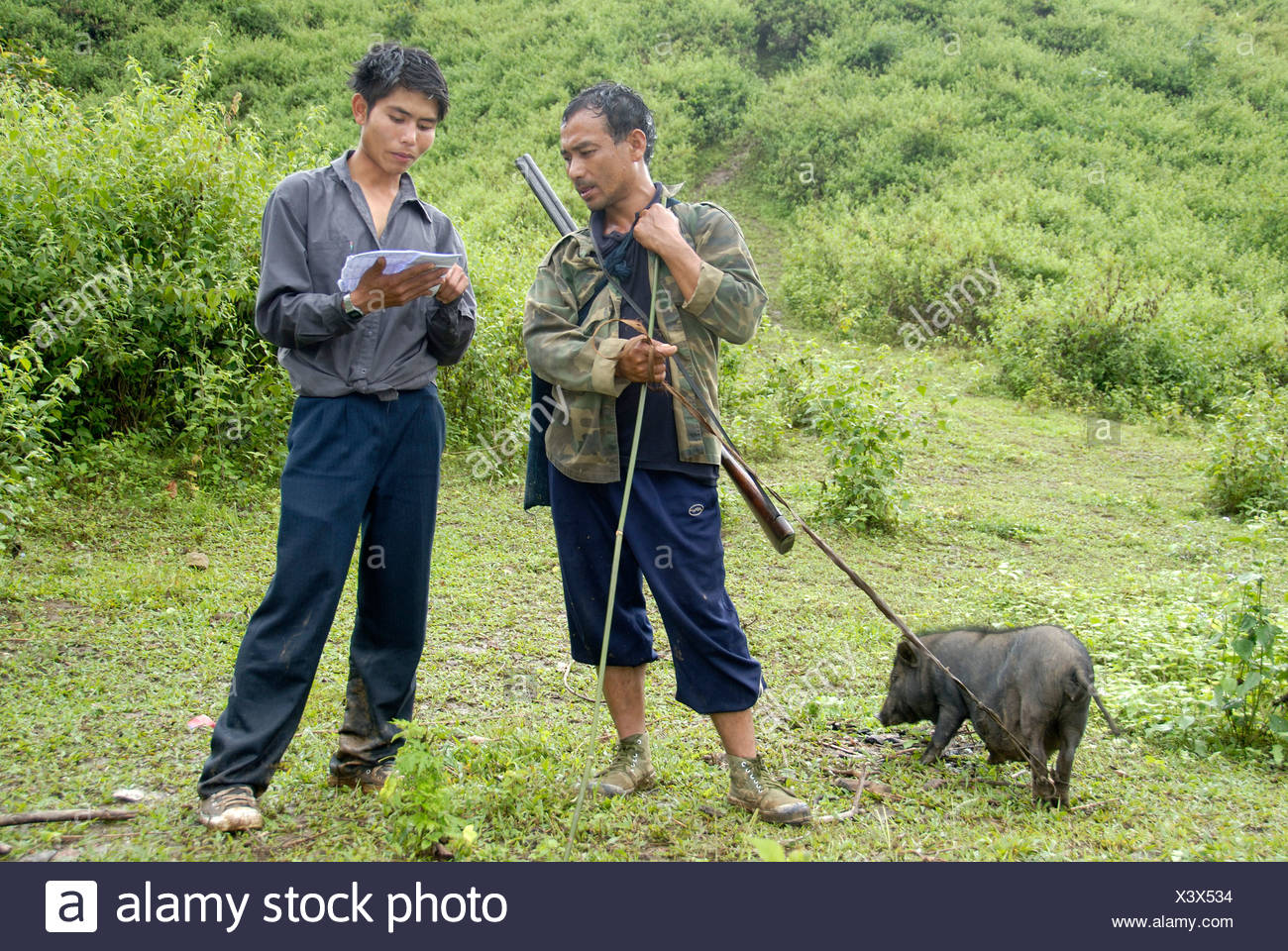 Laotians in conversation, the man Pixor Akha ethnic group with pork and a rifle in the wilderness, rifle, hunting, Phongsali di - Stock Image